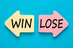 Win or lose written on two paper arrows on blue background. Business concept.