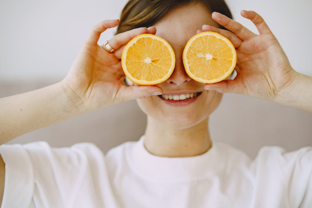 Woman hold slices of orange over her eyes.